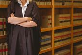 Lawyer leaning on shelf with arms crossed in library