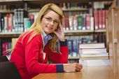 Smiling mature student studying at desk in library