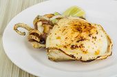 foto of cuttlefish  - Grilled cuttlefish with lime on the wooden background - JPG
