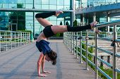 Girl stands on the hands, upside down. Acrobatics, ballet, dance