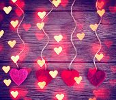 felt fabric love valentine's hearts hanging on rustic driftwood texture background with twine toned with a retro vintage instagram filter effect