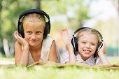 Cute girls in summer park listening to music