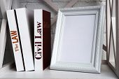 Photo frame with books on shelf, on brick wall background