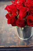 Beautiful red roses in a vase on wooden background