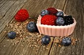 Pink chocolate dessert cup with berries on wood