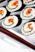Japanese Cuisine : Sushi Maki Roll with Vegetables and Salmon inside . on black dish with red and blue crabs .