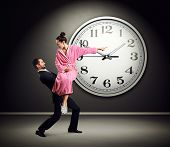 tired man carrying angry woman. young woman screaming and pointing at clock on dark wall