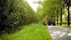 pic of grass-cutter  - mowing grass shoulder or verge along road in public space  with big orange tractor mower  - JPG