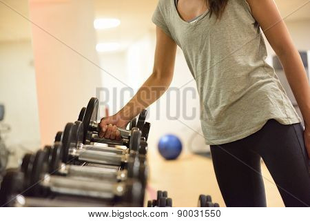 poster of Gym woman strength training lifting dumbbell weights getting ready for exercise workout. Female fitn