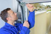 pic of garage  - Man installing a garage door - JPG