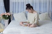 pic of short-story  - Girl sitting on the bed and reading a book - JPG