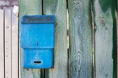 pic of mailbox  - Blue mailbox attached to old green fence - JPG