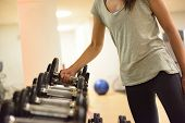 stock photo of strength  - Gym woman strength training lifting dumbbell weights getting ready for exercise workout - JPG