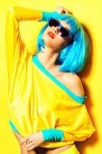 foto of wig  - Bright glamorous girl in vivid clothes and a wig alluring over yellow background - JPG