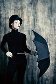 pic of top-hat  - Elegant male mime artist in top hat posing with umbrella by a grunge wall - JPG