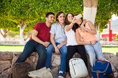 stock photo of mans-best-friend  - Bunch of college friends hugging each other and taking a selfie with a smartphone  - JPG