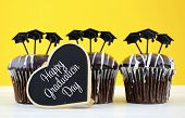 stock photo of graduation hat  - Happy Graduation Day party chocolate cupcakes with graduation cap hat topper decorations in yellow black and white party theme - JPG
