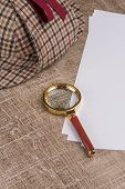 foto of private investigator  - Paper sheets and magnifying glass on Old Wooden table.