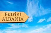 picture of albania  - Wooden arrow sign pointing destination BUTRINT ALBANIA against clear blue sky with copy space available - JPG