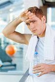 stock photo of forehead  - Tired young man with towel on shoulders looking at camera while holding bottle with water and touching his forehead - JPG
