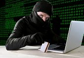 stock photo of hack  - man in black holding credit card using computer laptop for criminal activity hacking password and private information cracking password too access bank account data in cyber crime concept - JPG