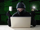 stock photo of illegal  - man in black holding credit card and lock using computer laptop for criminal activity hacking bank account password and private information cracking password for illegal access in cyber crime concept - JPG