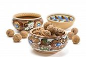 pic of ceramic bowl  - Ceramic bowl with floral ornaments with walnuts on a background of other dishes and nuts on a light background - JPG