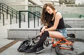 stock photo of swag  - Colorful outdoor portrait of young pretty fashion model with bike - JPG
