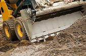 stock photo of skid  - Closeup skid steer loader excavator at road construction work - JPG