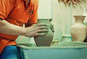 stock photo of loam  - On a rotating pottery wheel wizard manually manufactures ceramic vase - JPG