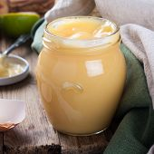 foto of curd  - Homemade lime curd in glass jar with fresh limes and egg shells on old wooden background - JPG