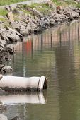stock photo of greenpeace  - sewage pipe polluting the water of a river - JPG