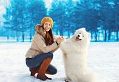 image of dog clothes  - Portrait of happy woman owner having fun with white Samoyed dog outdoors in winter day - JPG