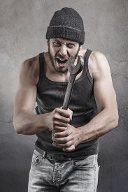 picture of hooligan  - Angry hooligan or thug shouting a threatening with a raised wrench during a violent crime or mugging over a grey background - JPG