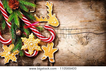 Christmas Holiday Background with Gingerbread cookies, Candy Cane and evergreens border over wooden