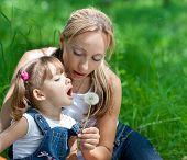 Mutter und Tochter In Jeans mit Löwenzahn im freien