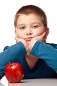 Young Boy Deciding To Eat A Healthy Apple