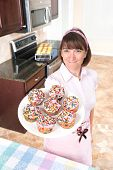 Homemaker Holding Plate Of Cupcakes