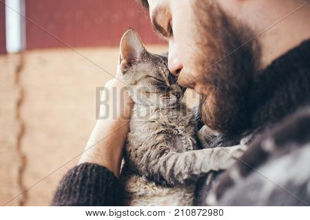 poster of Cat and man, portrait of happy cat with close eyes and young man, people playing with the kitten. Handsome Young Animal-Lover Man, Hugging and Cuddling his Gray Domestic Cat Pet