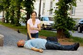 image of cpr  - Woman makes first aid for a man with heart attack in the street - JPG
