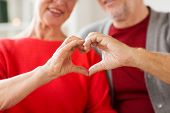 relationships, love and old people concept - close up of senior couple showing hand heart gesture poster