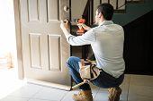 Young Man Fixing A Door Lock poster