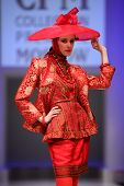 MOSCOW - FEBRUARY 22: A model wears a red suit and hat from Slava Zaytzev and walks the catwalk in C