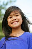 stock photo of 6 year old  - Six years old girl all smiles outdoors on a sunny day. Part Asian part Scandiavian background.