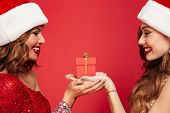 Close up portrait of two happy smiling women in christmas hats holding a gift box and looking at eac poster