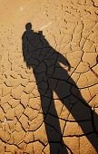 Silhouette of man over cracked drought land, result of global warming poster