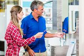 Shop assistant in hardware store counseling customer about lavatories for do-it-yourself project poster