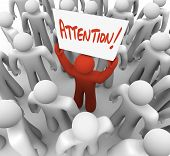 A red person stands out in a crowd holding a sign reading Attention, symbolizing the need to advertise to get noticed by your audience or customers