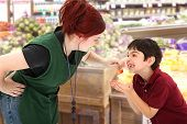 Grocery Clerk Giving Child Cherries In Store
