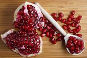Red Pomegranate Seeds Lie On A Wooden Spoon Next To A Piece Of Pomegranate. Ripe Seasonal Fruits poster